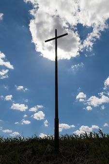 Croix haute contre le ciel bleu, l'éclairage crée un contour de la croix chrétienne