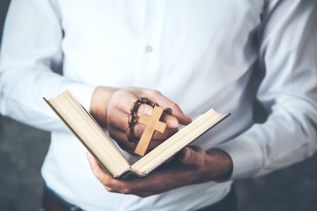 Croix de main de l'homme avec livre sur fond sombre