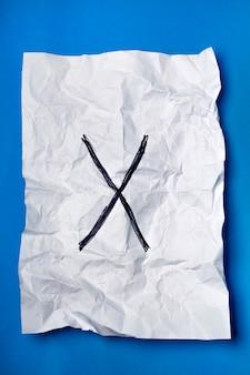 Croix noire sur un morceau de papier blanc froissé sur un fond bleu.
