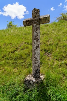 Croix de pierre sur le champ d'herbe verte.