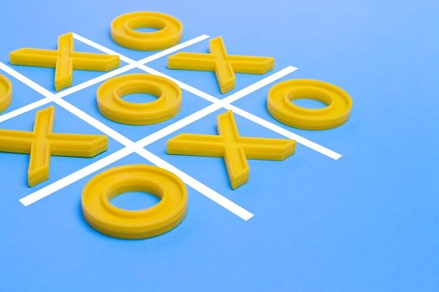 Croix en plastique jaune et un orteil et un champ réglé pour jouer au tic-tac-toe sur une surface bleue. concept xo win challenge. jeu éducatif pour les enfants