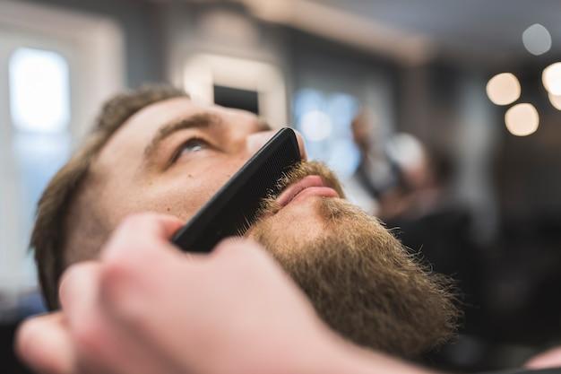Crop barber peignant la moustache du client