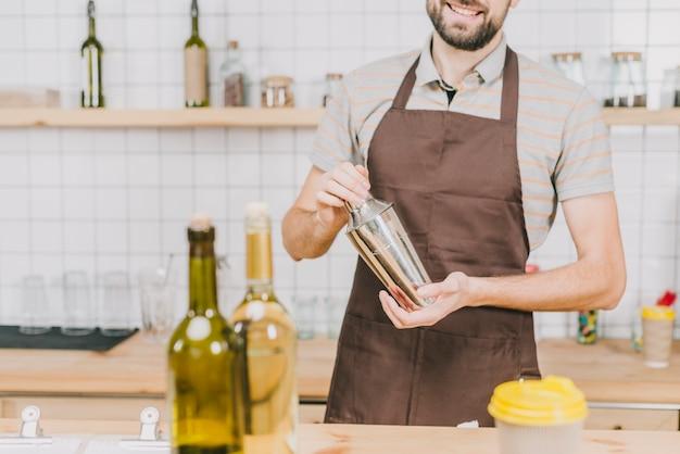 Crop barman faisant un cocktail