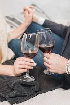 Crop couple amoureux tinter avec des verres à vin