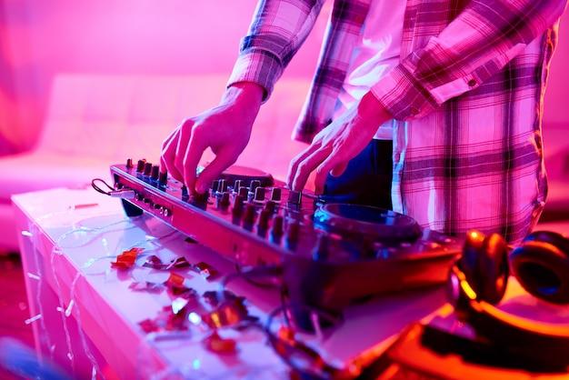 Crop dj jouant de la musique sur la table de mixage