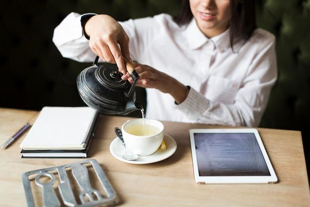 Crop femme ayant le thé pendant ses études