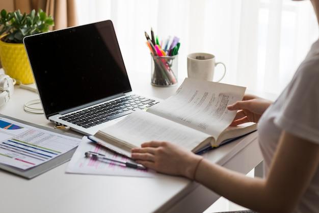 Crop femme lisant un livre au bureau
