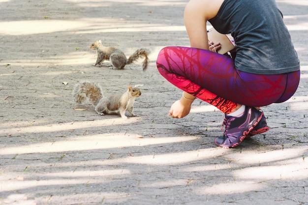 Crop femme nourrit des écureuils
