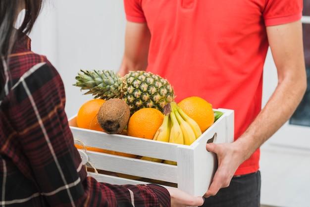 Crop femme prenant la boîte avec des fruits de messagerie