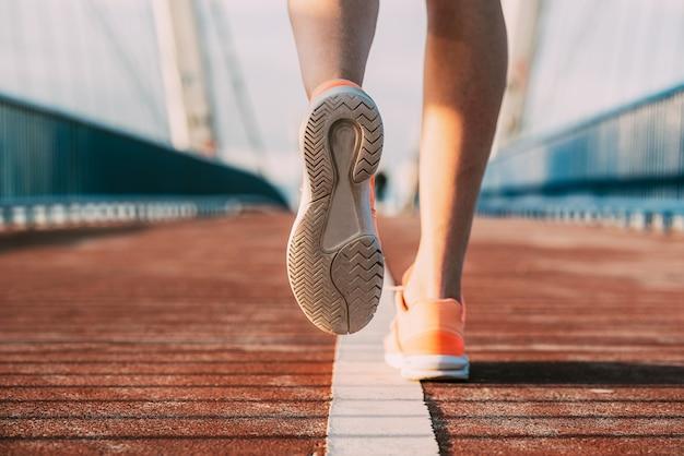 Crop femme qui court sur le pont