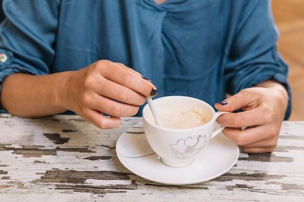 Crop femme en remuant le café