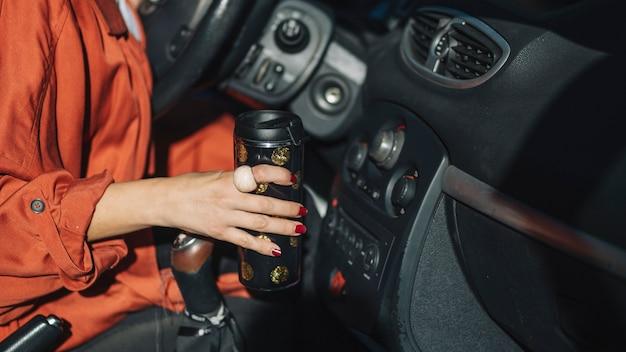 Crop femme avec thermos en voiture