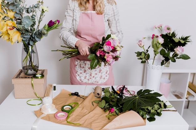 Crop femme travaillant avec des fleurs et du papier