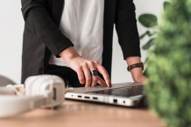 Crop femme utilisant un ordinateur portable au bureau
