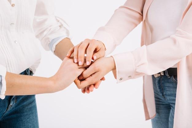 Crop femmes tenant par la main