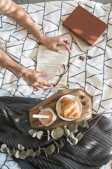 Crop hands avec livre près de la nourriture du petit déjeuner