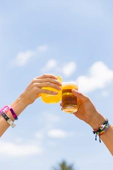 Crop hands mains tinter les verres avec des boissons