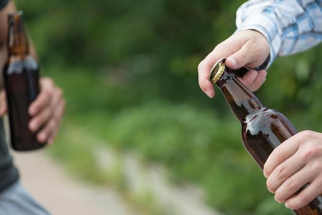 Crop hands ouvrant la bière près d'un ami