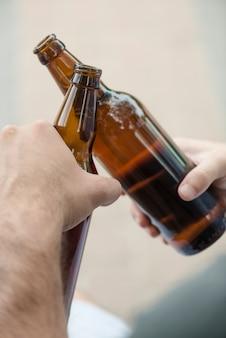 Crop hands tinter les bouteilles ouvertes
