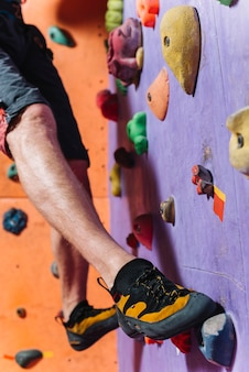 Crop jambes escaladant le haut mur