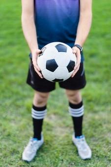 Crop jeune athlète avec ballon de football