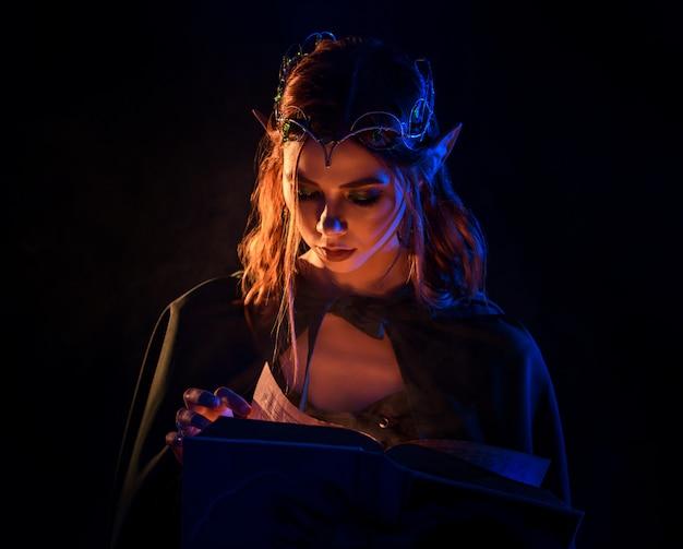 Crop de jeune charmante elfe aux cheveux roux regardant livre.