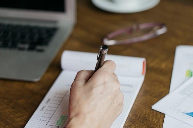 Crop main faisant des notes près d'un ordinateur portable