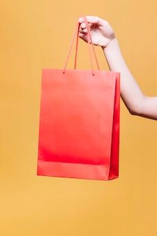 Crop main féminine tenant un sac en papier