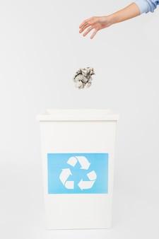 Crop main jetant du papier dans la poubelle