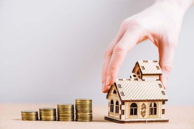 Crop main mettant la maison près de pièces de monnaie