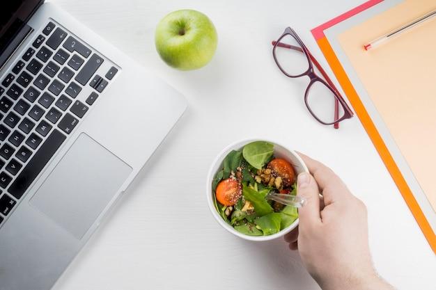 Crop main mettant la salade près d'un ordinateur portable