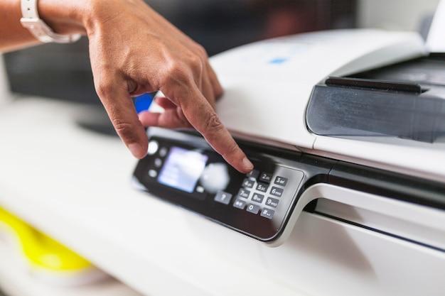 Crop main poussant des boutons sur l'imprimante