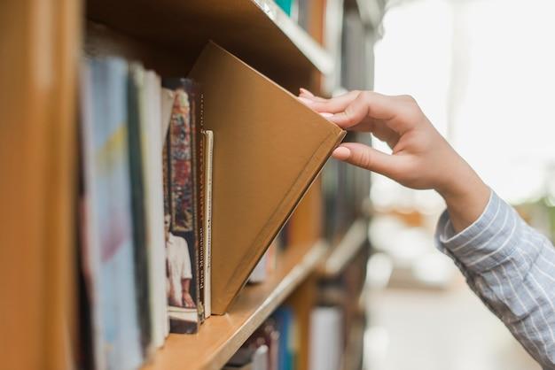 Crop main prenant le livre de la bibliothèque