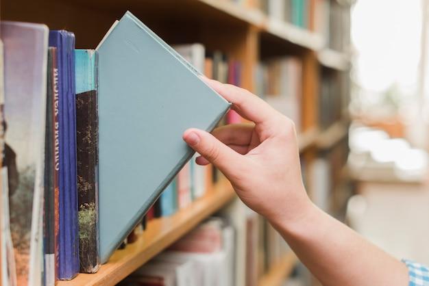 Crop main prenant le livre de l'étagère