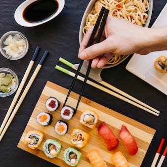 Crop main prenant des sushis à bord