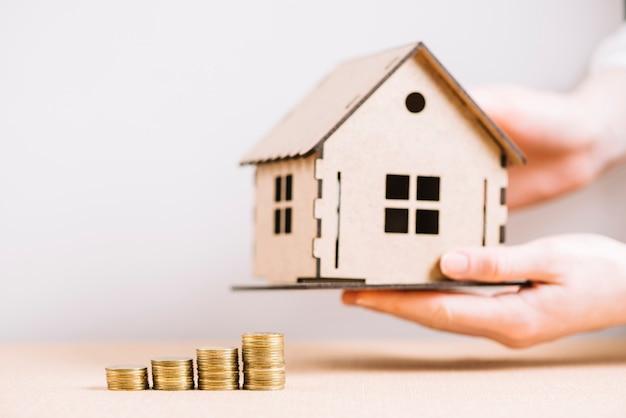Crop main tenant la maison près de pièces de monnaie