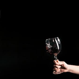Crop main tenant un verre de vin