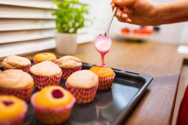 Crop main verser la sauce sur les muffins