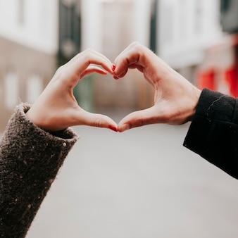Crop mains faisant le geste du cœur