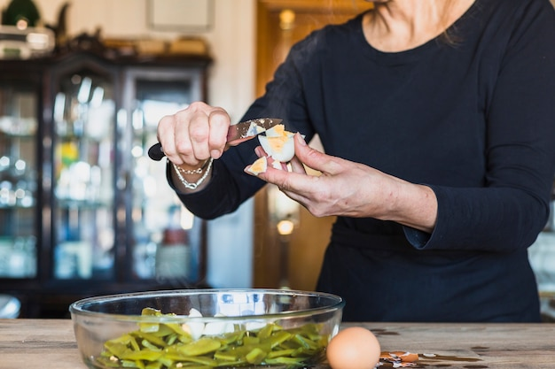 Crop mains d'une femme âgée cuisine plat délicieux dans la cuisine