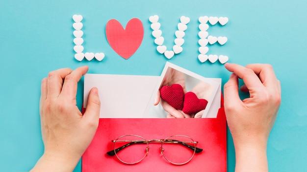 Crop mains ouverture enveloppe près de l'écriture d'amour