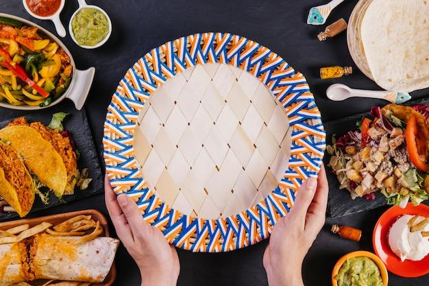 Crop mains tenant une assiette près de la nourriture mexicaine