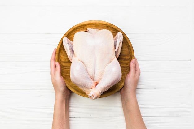 Crop mains tenant le poulet habillé
