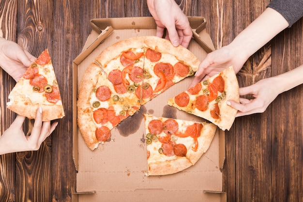 Crop mains tenant des tranches de pizza