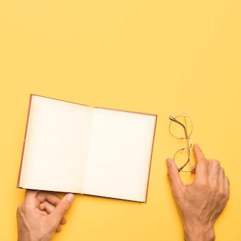 Crop male holding lunettes et cahier ouvert