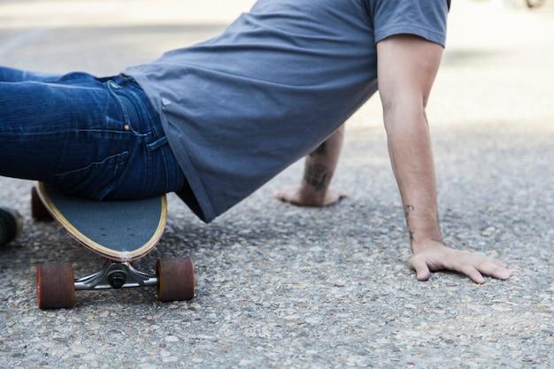 Crop man assis sur longboard sur le trottoir