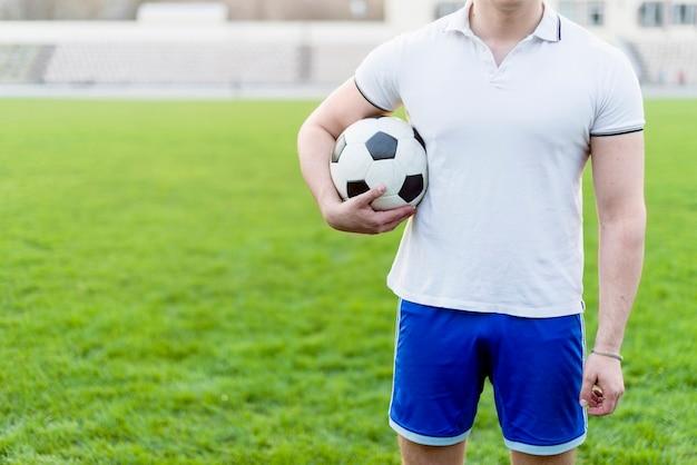 Crop man avec ballon de football sur le stade