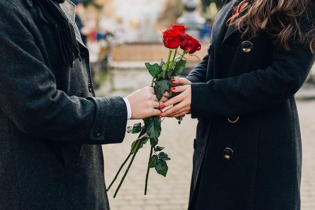 Crop man donnant des fleurs à la petite amie