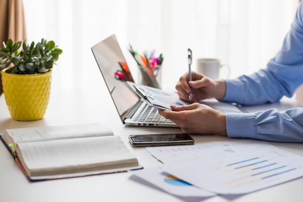 Crop man écrit dans les documents au bureau