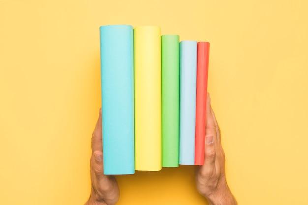 Crop man holding ordonné ensemble de livres